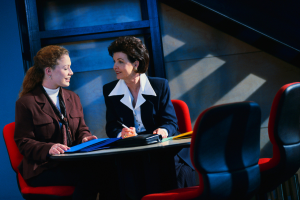 Photograph of two women conferring at a table.